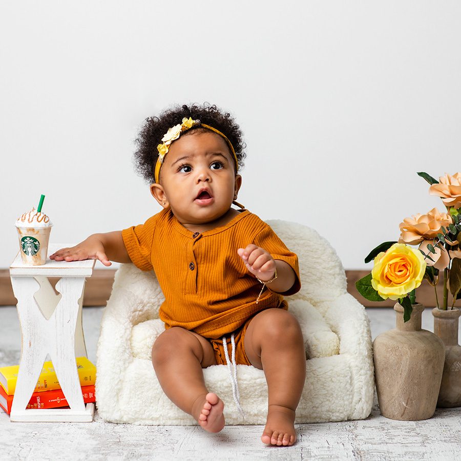 baby girl sitting on sherpa couch with starbucks Frappuccino